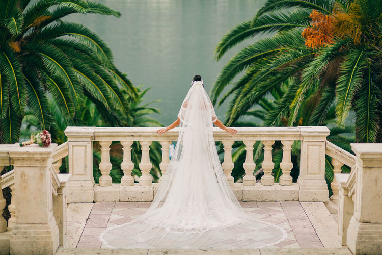 Rear View Of Bride Standing At Balcony