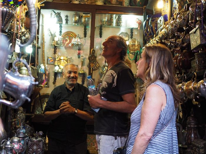 People And Places my uncle back at his childhood hometown of Marrakech in a shop in the Medina , looking in awe with my aunt.