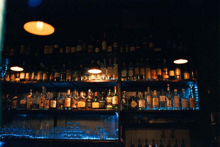 Illuminated bottles on display at night