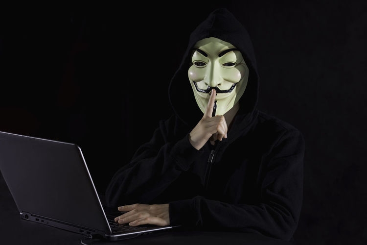 Portrait of computer hacker wearing mask with finger on lips against black background