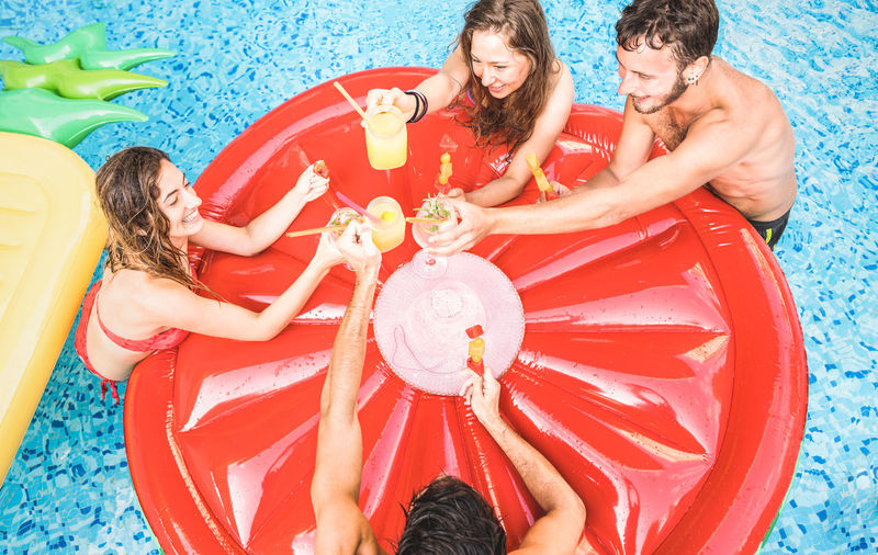 Top view of happy friends drinking cocktails with fruit at swimming pool party - Vacation concept with guys and girls having fun at summer luxury resort - Young people cheering at tropical beach Friends Friendship Young People Teenagers  Millenials Summer Vacation Swimming Pool Luxury Resort Vacations Holidays Fun Having Fun Beach Party Ibiza Happy Happy Hour Cocktails Drinking Lifestyle Bikini