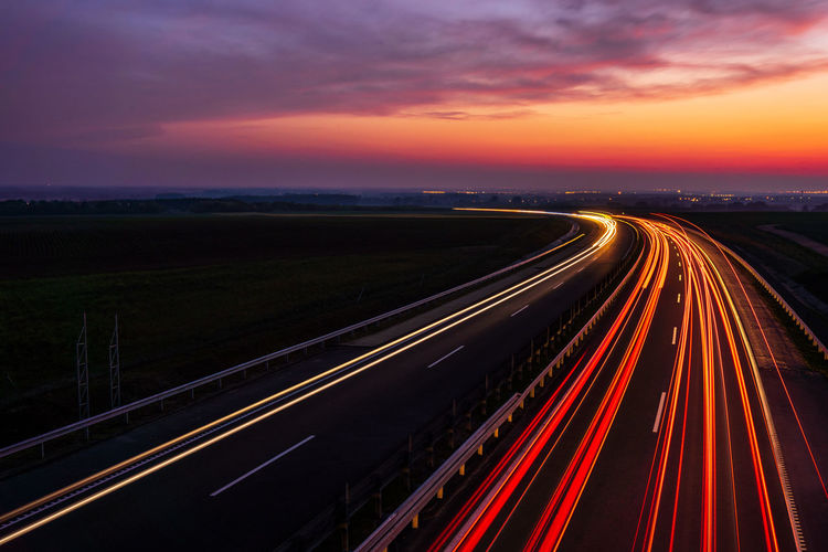High angle view of light trails on road against sky at sunset