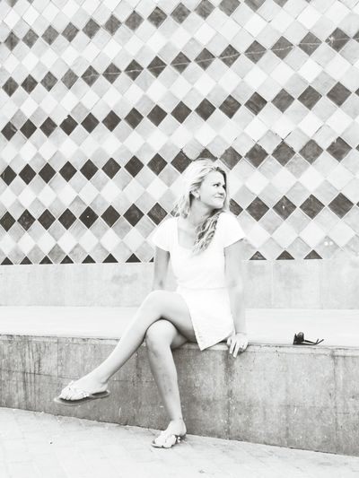 Happy young woman sitting against wall