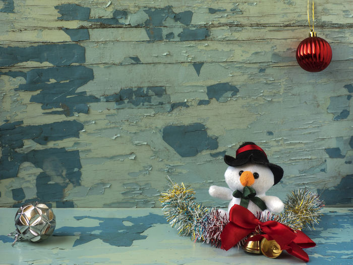 Snowman Toy With Ornaments On Table During Christmas