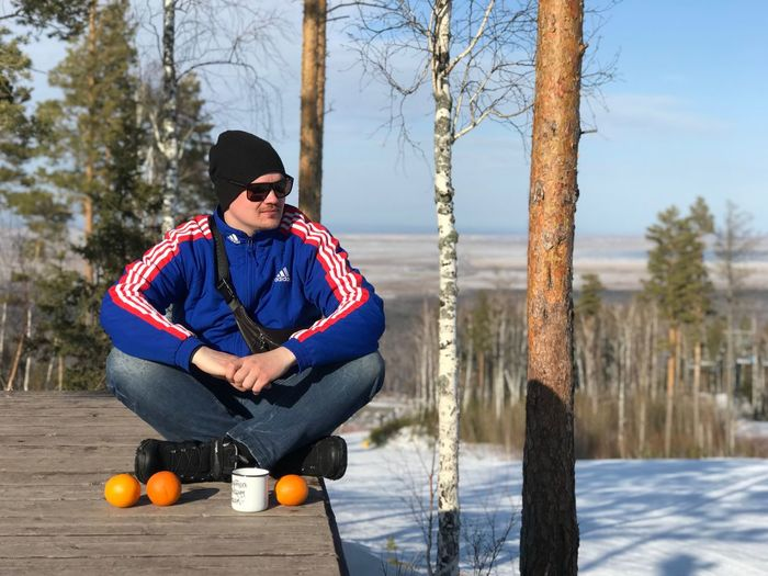 Young man sitting in park during winter