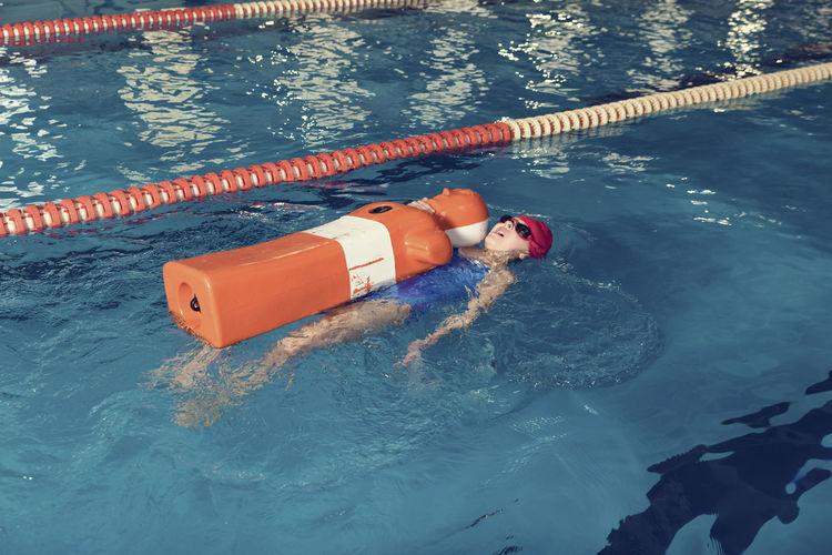 Girl with cpr dummy swimming in pool