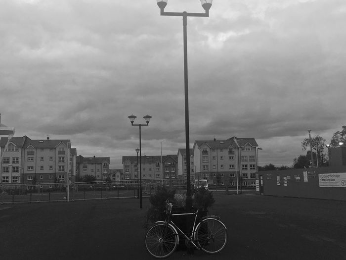 Bicycle parked on road against cloudy sky
