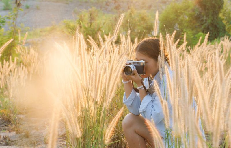 Plant Photography Themes One Person Photographing Land Leisure Activity Women Outdoors Day Activity Holding Lifestyles Nature Field Sunlight Real People Technology Camera - Photographic Equipment