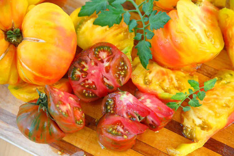 Ripe heirloom tomatoes from overhead Food Healthy Eating Studio Shot Indoors  No People Close-up Freshness Heirloom Tomatoes Vegetables Food Preparation Juicy Ripe Fresh Produce Textures Leaves Cutting Board Overhead Natural Light Colorful Yellow Red Nutritious Summer Food Seasonal