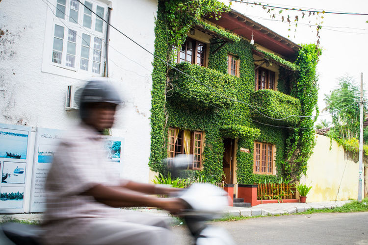 motorbike rider speeds past ivy covered house - Cochin, India. Adult Architecture ASIA Bike Building Exterior Cochin House India Ivy Kerela Lifestyles Moped One Person Outdoors Travel