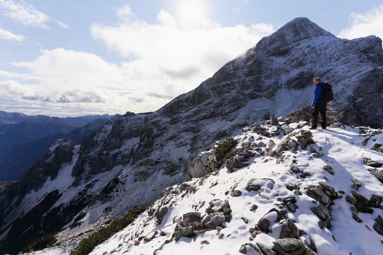 Rear view of people hiking on snowcapped mountain in triglav national park in slovenia