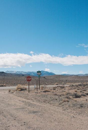Road sign in desert against blue sky