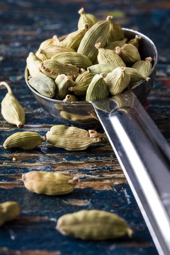 Close-up of cardamoms in spoon on table