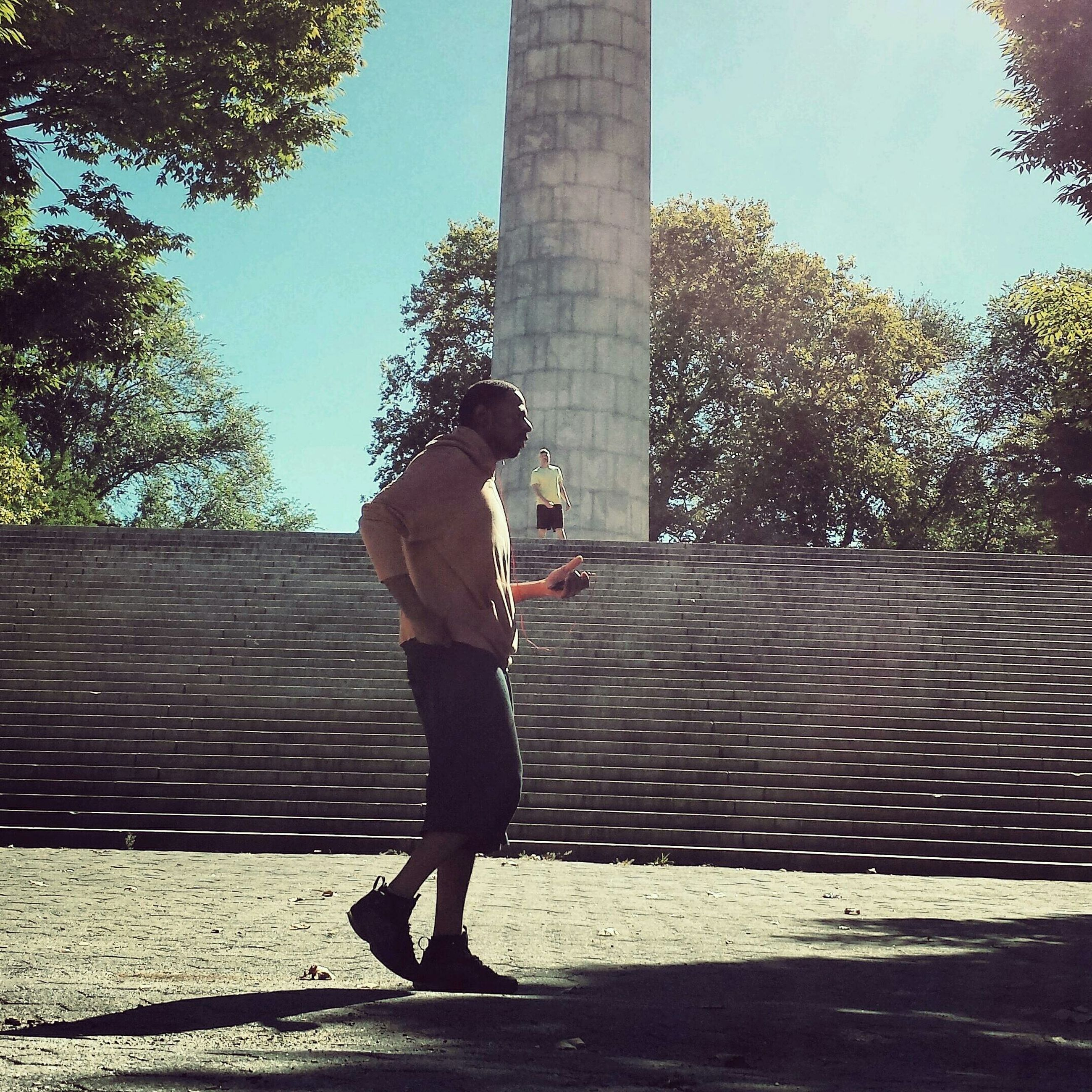 full length, lifestyles, tree, casual clothing, leisure activity, sunlight, walking, shadow, person, standing, clear sky, young adult, rear view, day, childhood, street, built structure, outdoors