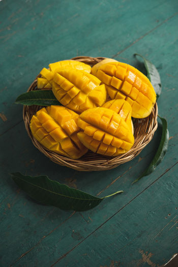 Mango in a basket on a green wood Food Food And Drink Yellow Freshness Table Still Life Healthy Eating No People Container Close-up Vegetable Wellbeing High Angle View Corn Basket Wood - Material Day Outdoors Raw Food Fruit Sweetcorn Temptation