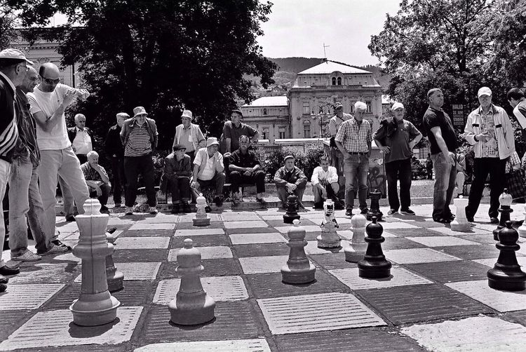 The Storyteller - 2014 Eyeem Awards Community Chess   Every afternoon the wise old men of Sarajevo gather to pit their wits against each other in a game of chess. It is a lively community affair that sees spectators shouting their approval or disagreement with the players' decisions, sometimes striding onto the chess set to demonstrate what they think would be a better plan of attack. Sarajevo Travel Black & White