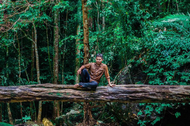 Full length of man sitting on fallen tree trunk in forest