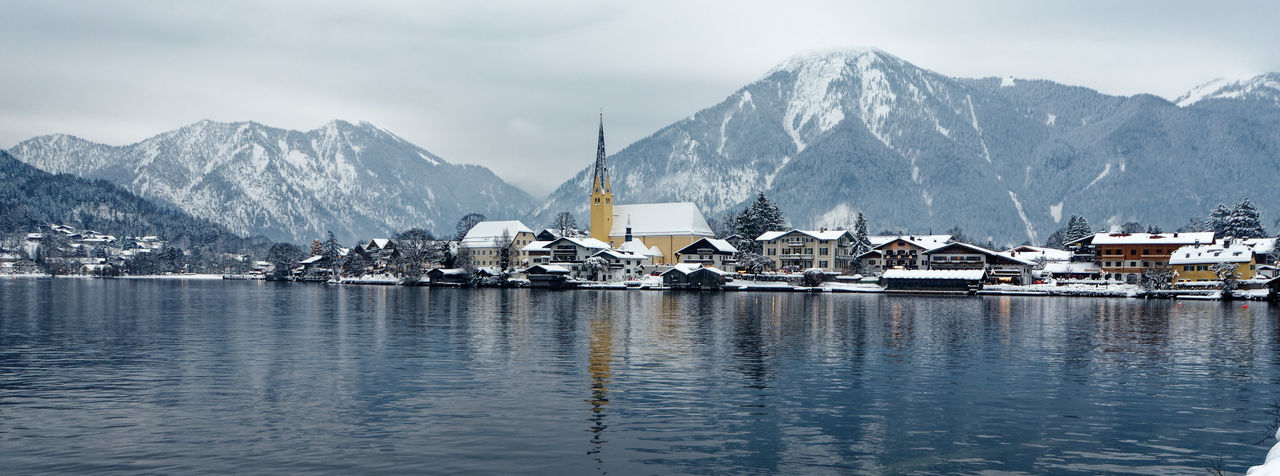 Village in bavaria by snowcapped mountains at s lake against sky during winter