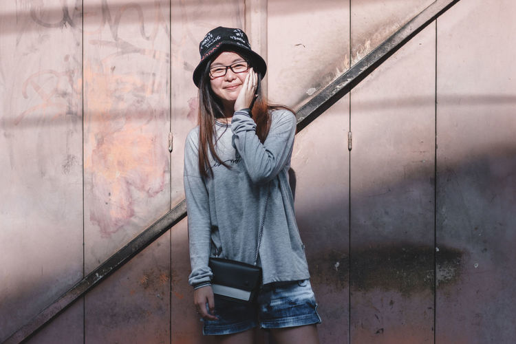 Real People One Person Young Adult Leisure Activity Front View Casual Clothing Young Women Lifestyles Smiling Standing Wall - Building Feature Portrait Architecture Clothing Three Quarter Length Looking At Camera Built Structure Emotion Hair Beautiful Woman Hairstyle Outdoors
