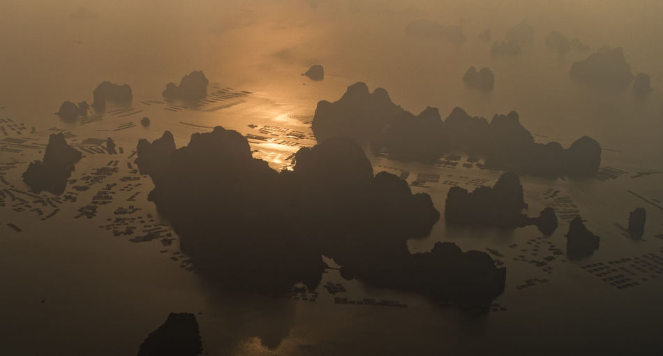 High angle view of rock formations in sea during sunset