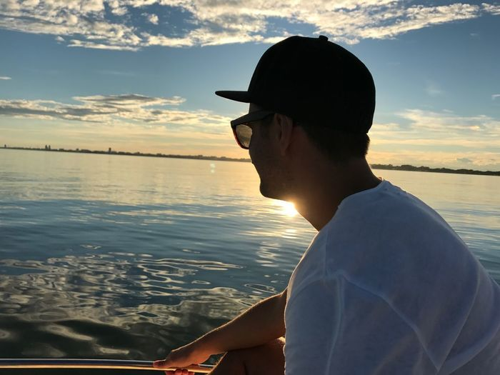 Sunlight Blue Sky White T-shirt Italy Summer On Boat Summer Summertime EyeEmNewHere Man On Boat Man Boat One Person Water Sea Sunset Sunglasses Headshot Leisure Activity Sky Real People Lifestyles Cloud - Sky Outdoors Side View Horizon Over Water Nature Men Scenics