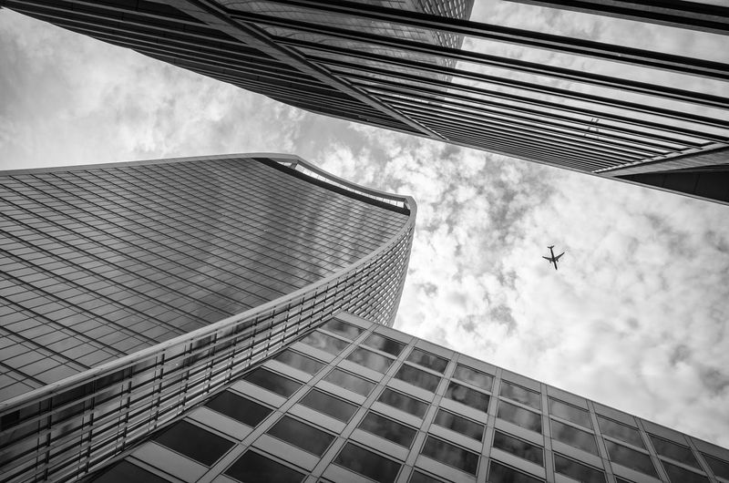 Airplane passing over a modern building office center in London Architecture Aviation Blackandwhite Building Building Exterior Built Structure City Cloud - Sky Day Financial District  Flying Low Angle View Nature No People Office Office Building Exterior Outdoors Skyscraper Tall - High Tower