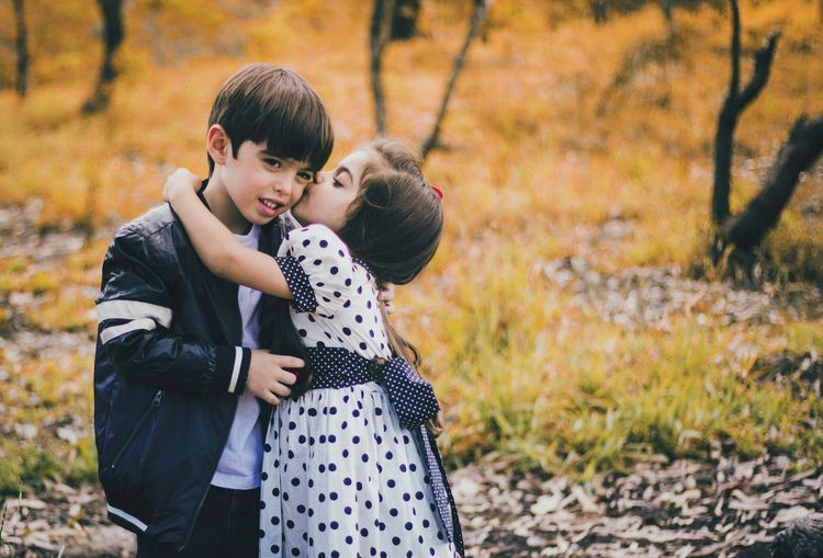 Sister Kissing On Brother Cheek At Forest