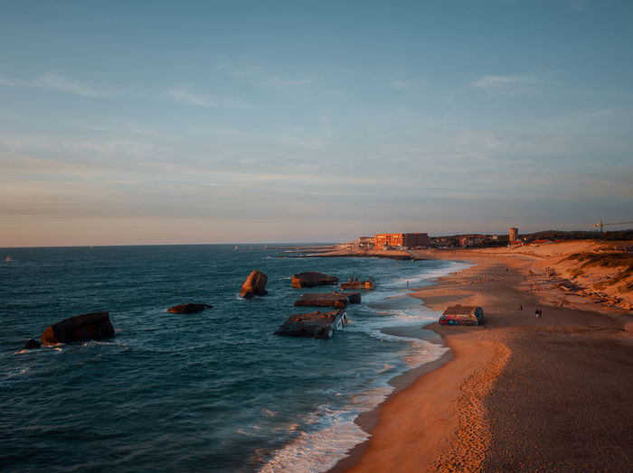 Scenic view of sea against sky during sunset with ruins of bunkers in foreground