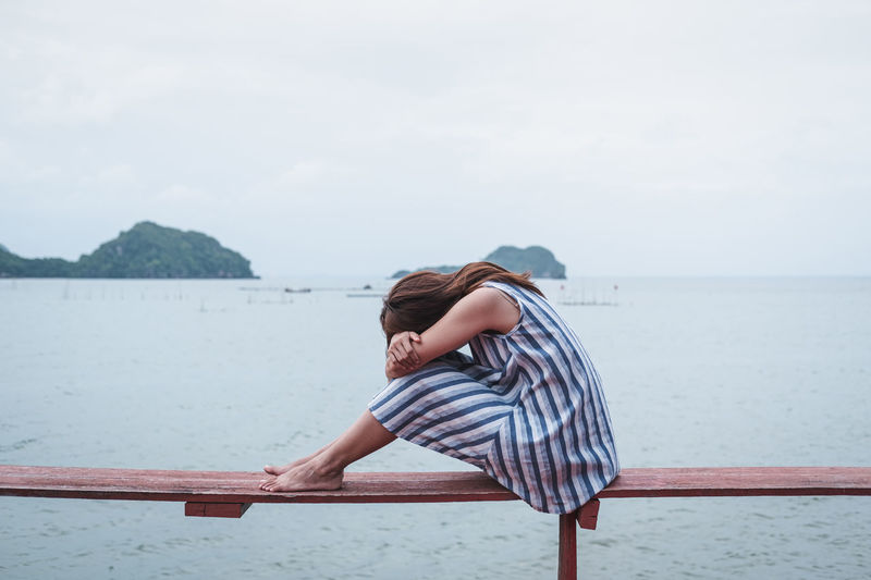 Woman sitting on railing by sea against sky