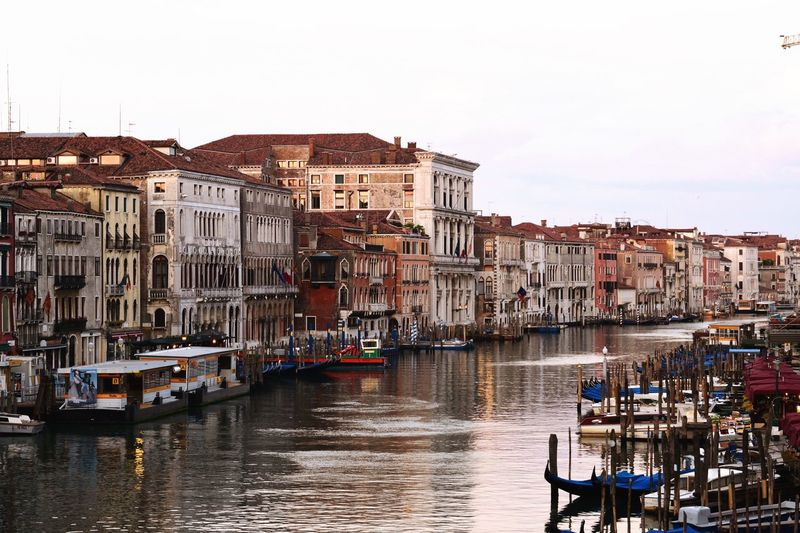 Boats in canal amidst buildings in venice