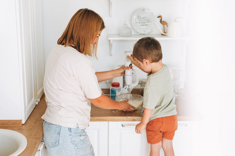 Young woman mother and her toddler boy son cooking with blender at the table in kitchen at home