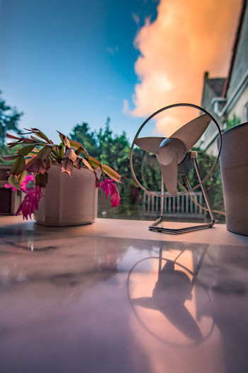 Close-up of electric fan and potted plants on window sill