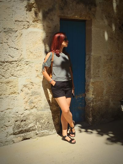 Full length of young woman standing against wall