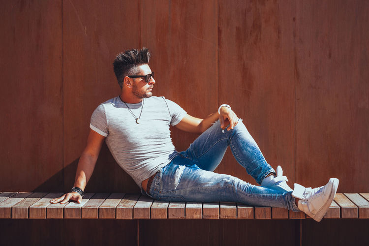 Casual Clothing One Person Young Men Sitting Full Length Wood - Material Young Adult Real People Lifestyles Wall - Building Feature Leisure Activity Men Front View Looking Beard Day Looking Away Relaxation Facial Hair Jeans