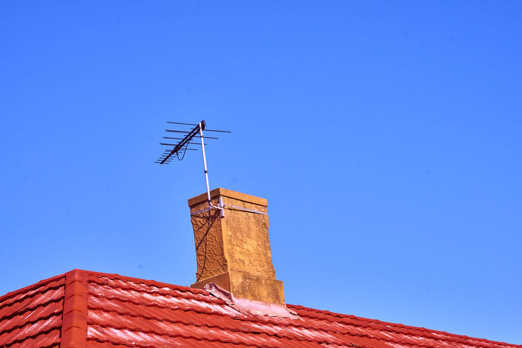Antenna - Aerial Architecture Blue Building Building Exterior Built Structure Chimney Clear Sky Communication Copy Space Day High Section Low Angle View Nature No People Outdoors Roof Roof Tile Sky Sunlight Technology