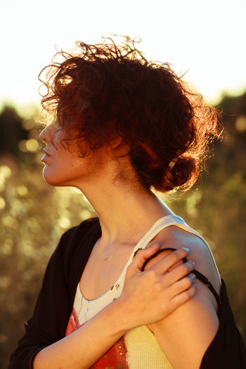 Side view of woman with messy hair standing on field during sunny day