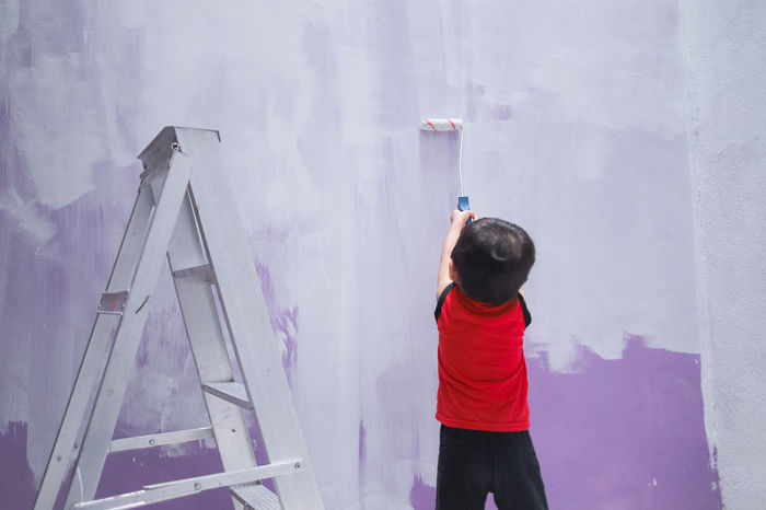 Childhood Day Indoors  Leisure Activity Lifestyles One Person Paint Roller People Real People Rear View Skill  Standing