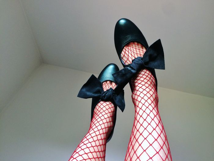 Low section of woman wearing stockings and shoes against wall