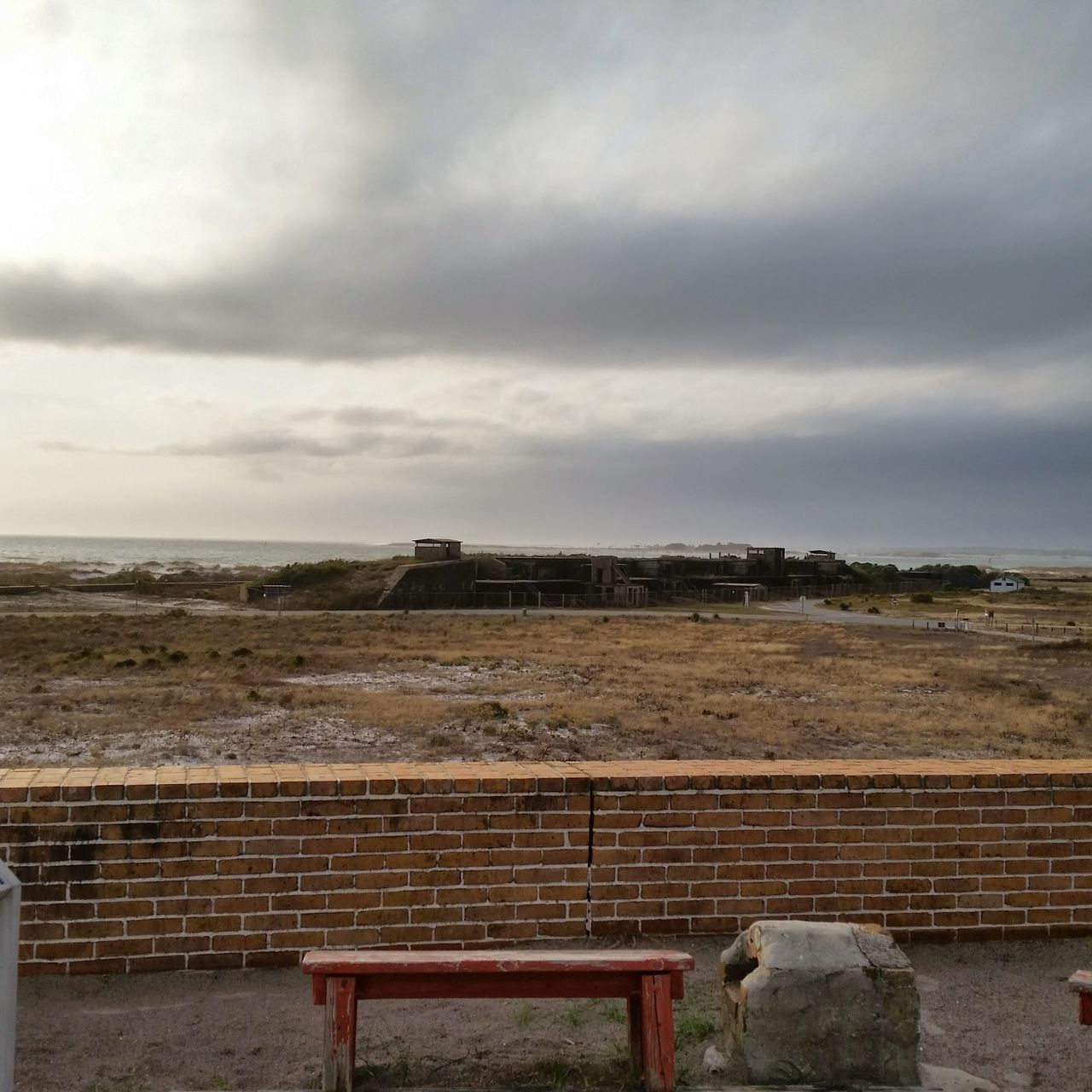 Empty Bench At Fort Pickens Against Cloudy Sky