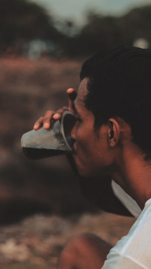 Side view of man drinking juice