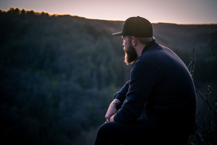 Side view of young man looking at mountain during sunset