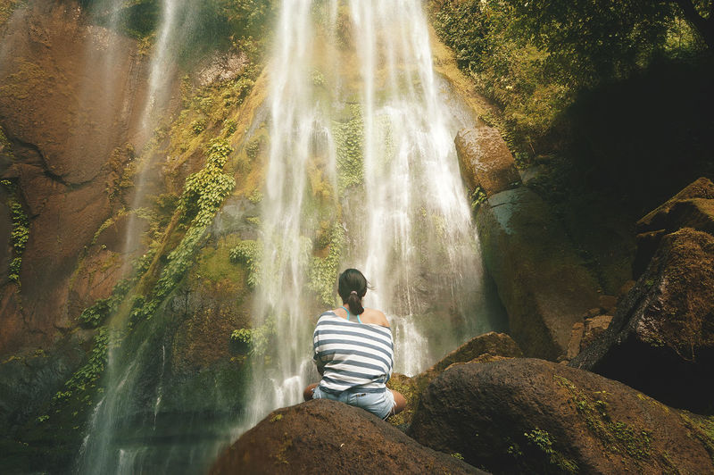 Rear View Of Woman Sitting At Waterfall