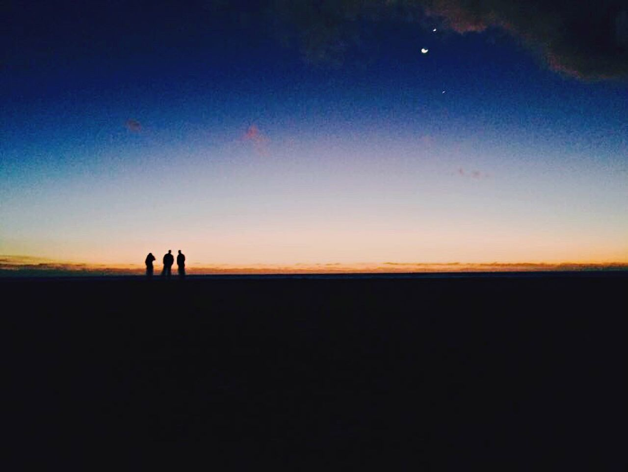 SILHOUETTE OF PEOPLE ON SEA AT SUNSET