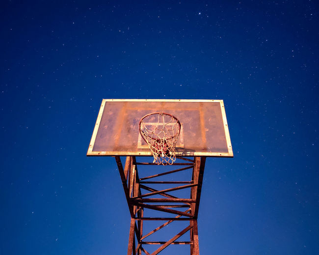 Nocturnal view of basketball post hoop