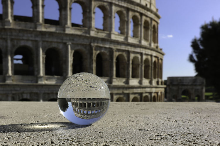 Close-up of crystal ball against colosseum