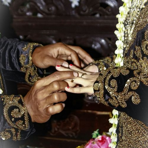 Midsection Of Bridegroom Putting Ring On Woman Finger In Wedding Ceremony