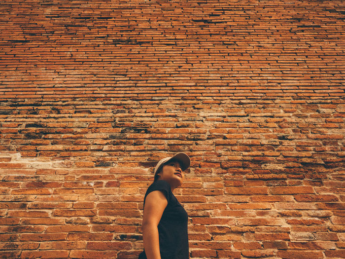 Low angle view of woman standing by brick wall