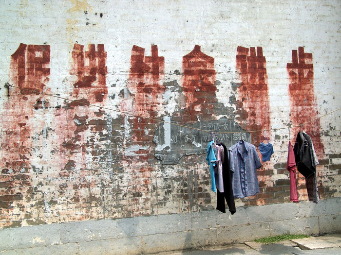 Clothes hanging on clothesline against brick wall