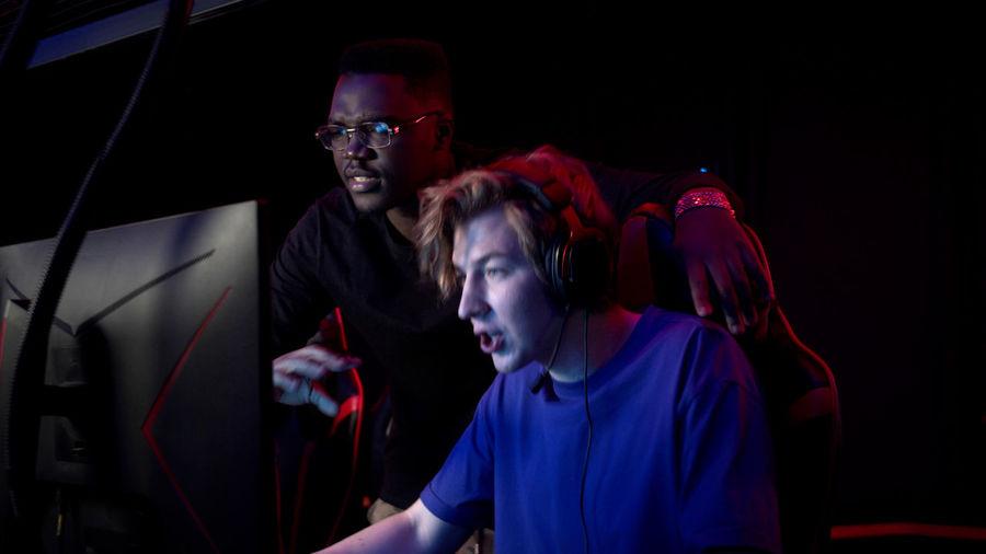 Men playing video game in darkroom