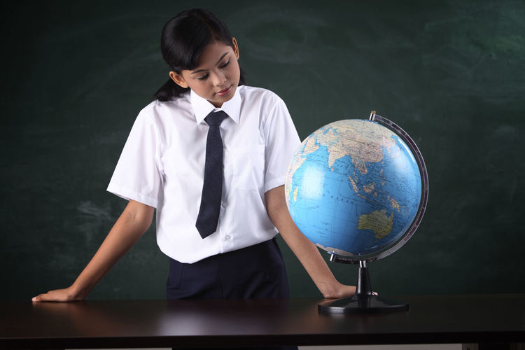 Schoolgirl with globe against blackboard